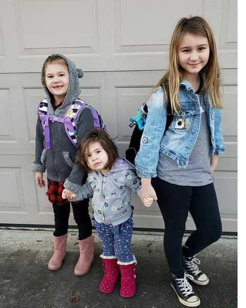 RACHELLE DOMINGUEZ - Cora Sutton (left) poses with her two sisters, Aliviya Dominguez and Marlie Sutton, on Monday, Jan. 14, her first day back to elementary school since undergoing a heart transplant in September.