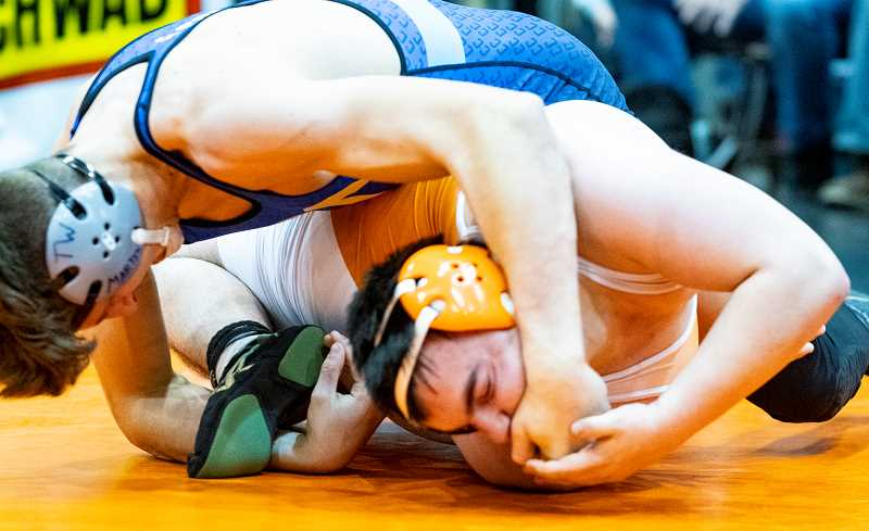 LON AUSTIN/CENTRAL OREGONIAN - Jaxson Rhoden works to pin Cooper Hise of Dallas during the Oregon Wrestling Classic championship round. Rhoden, who normally wrestles 195 pounds, dominated the match, but the Cowboys fell to the Dragons 38-29 as Dallas took the tournament championship.