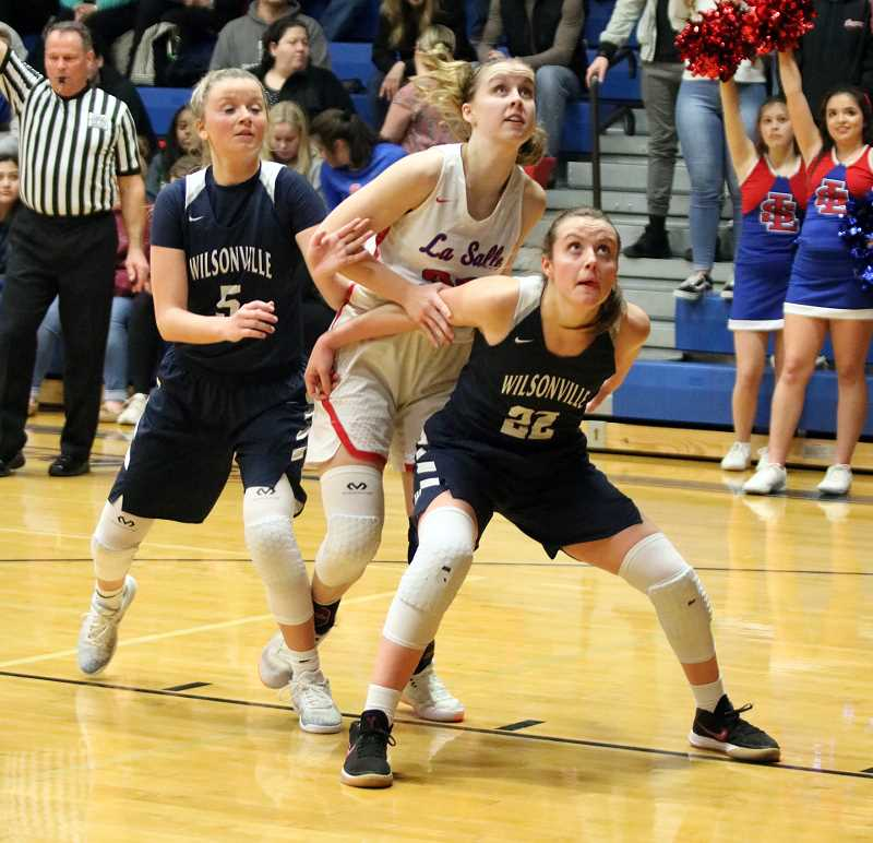 PAMPLIN MEDIA GROUP PHOTO: JIM BESEDA - Wilsonvilles Cydney Gutridge (22) boxes out against La Salle Preps Lauren Vreeken as Reese Timm backs up the play.