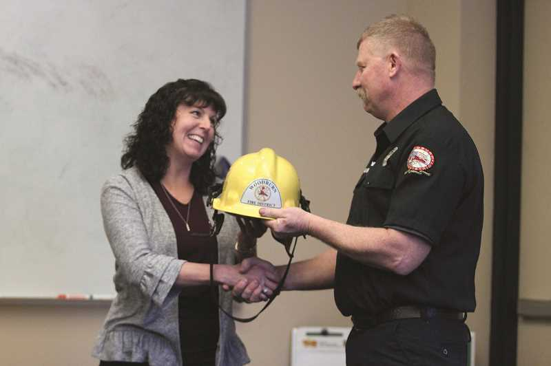 PHIL HAWKINS - Former Metcom Director Gina Audritsh accepts an outgoing gift from Woodburn Fire District's Robb Gramzow  at Audritsh's retirement party last week.