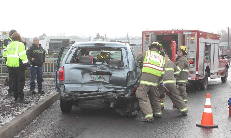 SUSAN MATHENY/MADRAS PIONEER - Fire personnel worked to pry open a door to assist a passenger in the Dodge Caravan vehicle following an accident Jan. 17, at the Highway 26/97 intersection near Sonic Drive-In.