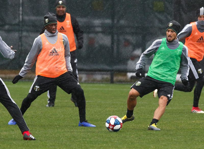 TRIBUNE PHOTO: JONATHAN HOUSE - Diego Chara (left) and Sebastian Blanco hone their first-day form during a rainy Portland Timbers workout on Tuesday in Beaverton.