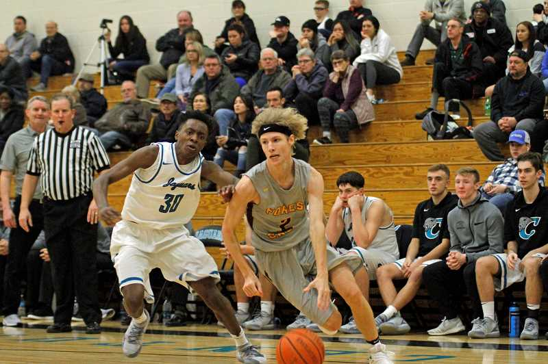 STAFF PHOTO: WADE EVANSON - Forest Grove's J.J. Buehler drives around a Century's Edy Essien (30) during the Vikings' game against the Jaguars Tuesday, Jan. 22, at Century High School.