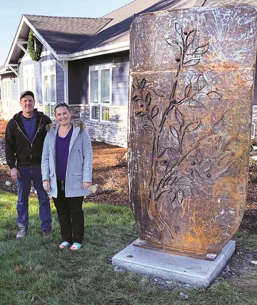 CAROL ROSEN - Dr. Olesya Salathe, right, of The Dentist Off Main, stands with sculptor Ben Dye. The sculpture is a picture of Huckleberries that the Molala (sic) tribe used in cooking along with the roots for medicine.