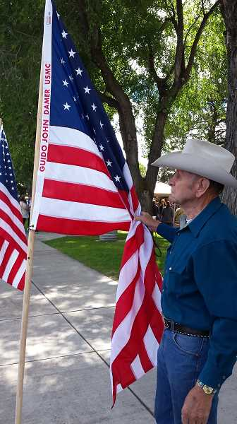 PHOTO COURTESY OF THE DAMER FAMILY  - Prineville resident Guido Damer finds the Flags of Prineville United States flag with his name during the Crooked River Roundup festivities. Damer served in the United States Marine Corps from 1961 to 1964.