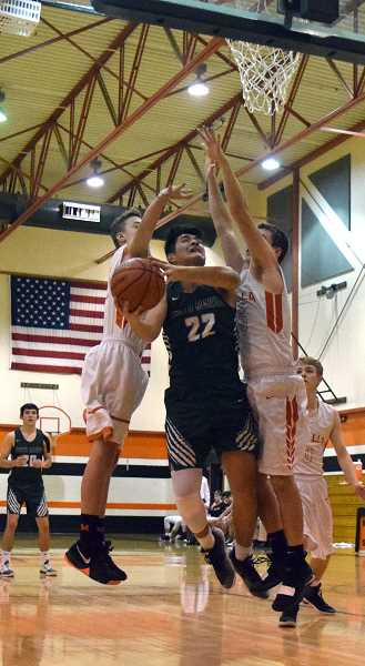 HERALD PHOTO: TANNER RUSS - North Marion's Sergio Jimenez battles to the hoop against the Molalla defense.