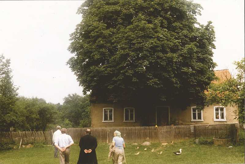 PHOTO COURTESY OF THE DAMER FAMILY   - This 1988 photo shows the Damer family home in Guhren, Germany. Pictured are Guido's cousin, an interpreter, a priest and the Polish lady who lived in the home at the time. The far right window is the room where all six Damer children were born.