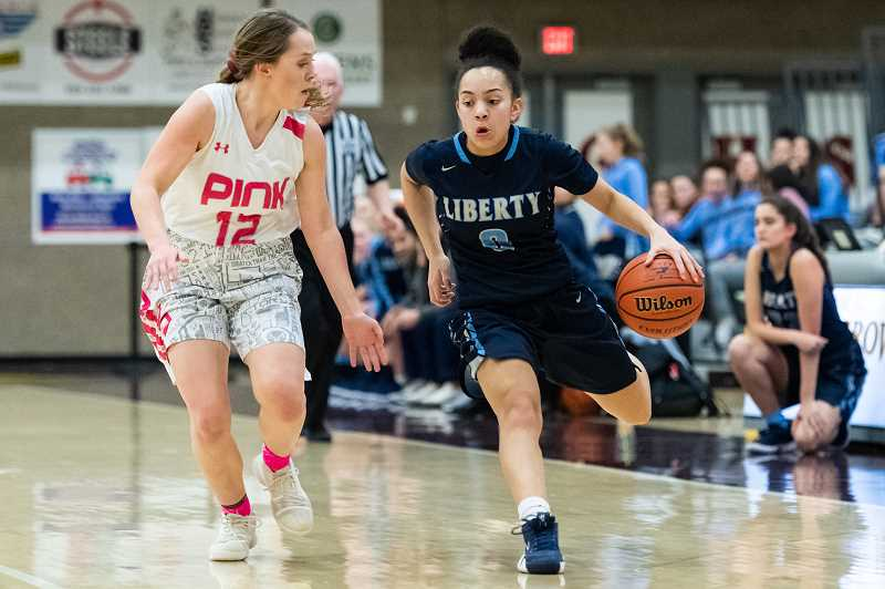 STAFF PHOTO: CHRISTOPHER OERTELL - Liberty's Taylin Smith attacks Forest Grove's Katie Ellington during the Falcons' game against the Vikings, Friday, Jan. 25, at Forest Grove High School.