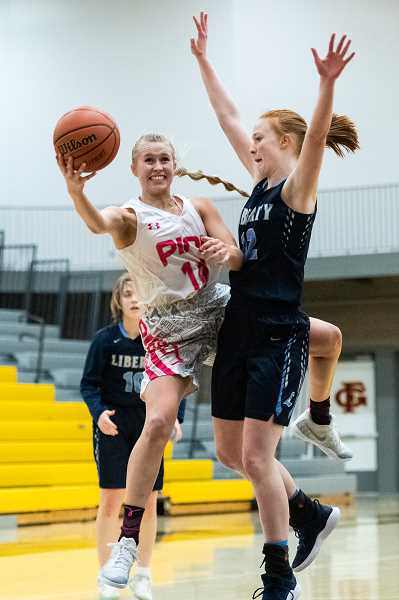 STAFF PHOTO: CHRISTOPHER OERTELL - Forest Grove's Amanda Rebsom scoops a shot around Liberty's Breeze Bartle during the Vikings' game against the Falcons, Friday, Jan. 25, at Forest Grove High School.
