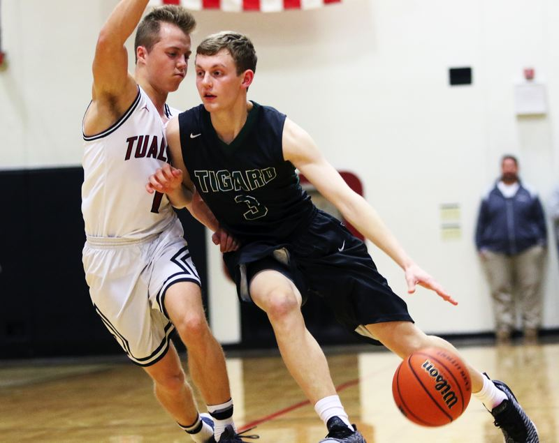 TIMES PHOTO: DAN BROOD - Tigard senior Jake Bullard (right) tries to drive against Tualatin senior Caden Dickson during Friday's Three Rivers League game.