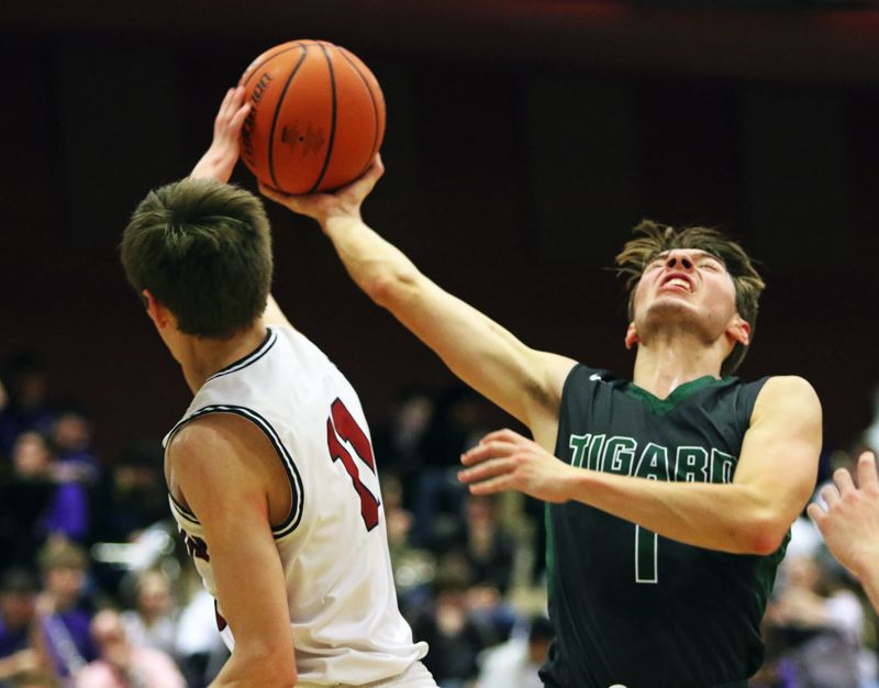 TIMES PHOTO: DAN BROOD - Tigard senior Diego Lopez (right) and Tualatin senior Jason Wisler battle for the ball during Friday's Three Rivers League contest.