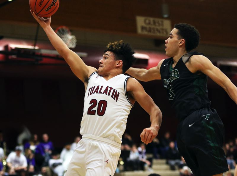 TIMES PHOTO: DAN BROOD - Tualatin junior John Miller (20) goes to the basket against Tigard sophomore Drew Carter during Friday's game.