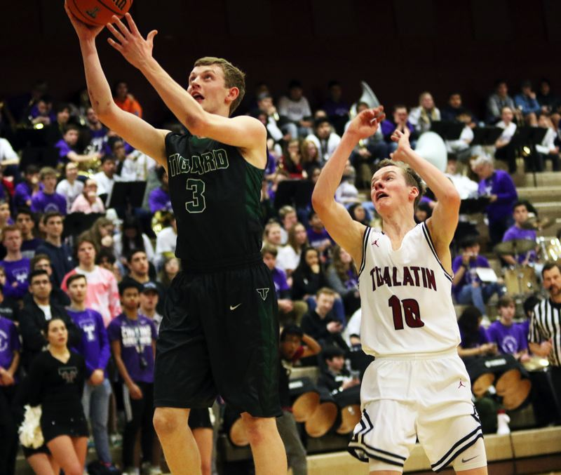 TIMES PHOTO: DAN BROOD - Tigard senior Jake Bullard goes to the basket for a layup after getting a steal during Friday's game at Tualatin.
