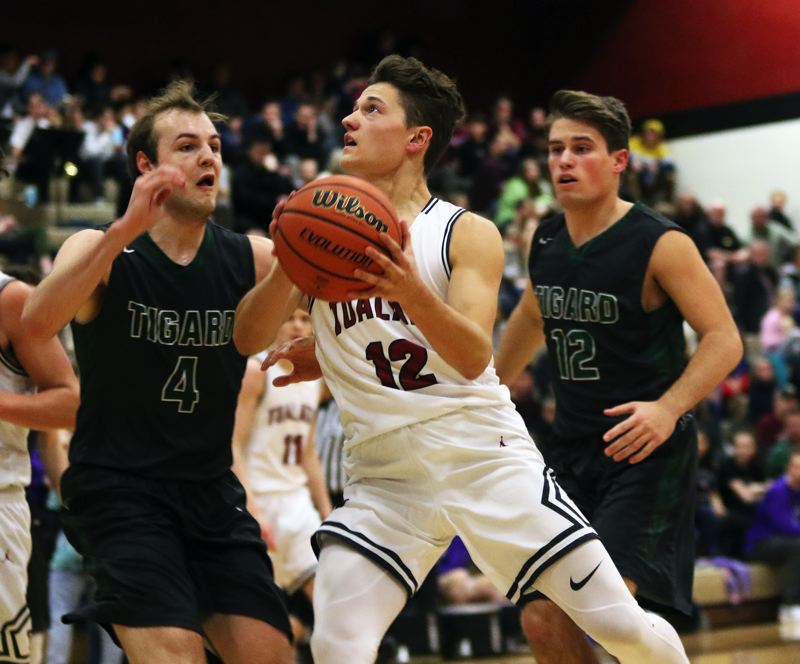 TIMES PHOTO: DAN BROOD - Tualatin junior Sam Noland (center) looks to go to the basket between Tigard seniors Stevie Schlabach (left) and Carson Crist during Friday's game.