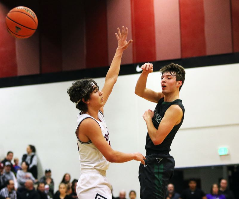 TIMES PHOTO: DAN BROOD - Tigard senior Diego Lopez (right) fires a pass past Tualatin senior Bridger Steppe during Friday's game.