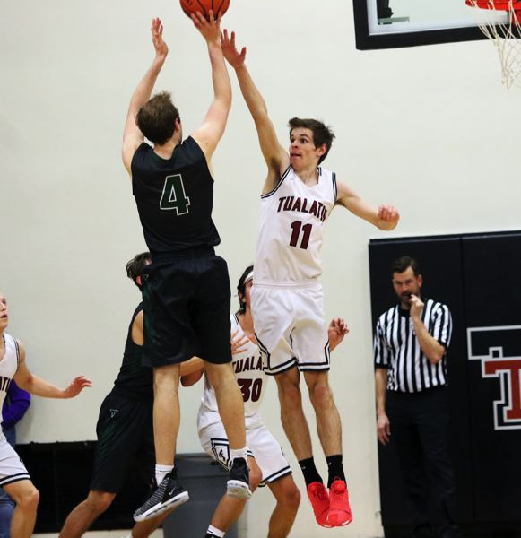 TIMES PHOTO: DAN BROOD - Tigard senior Stevie Schlabach (4) tries to shoot over Tualatin senior Jason Whisler during Friday's game.