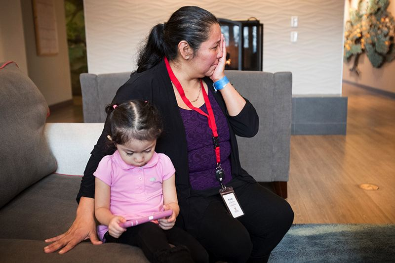 PORTLAND TRIBUNE: JAIME VALDEZ - Reina Quijada of Bend wipes tears from her eyes as she recalls her son receiving a big Legos set for Christmas during her stay at the Ronald McDonald's East House as her 2-year-old daughter Alexa plays on her phone.