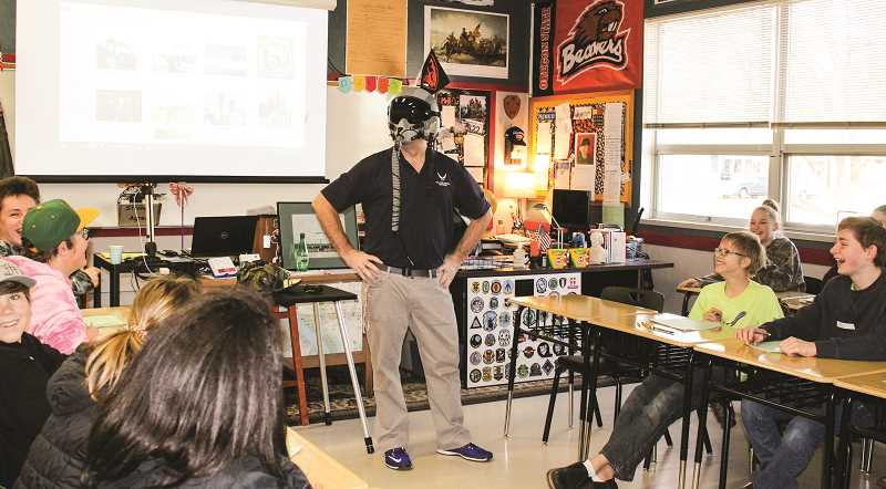 JASON CHANEY/CENTRAL OREGONIAN  - Scott Buchanan gets some laughs from eighth-grade students when he put on some gear during his military presentation Friday.