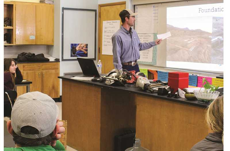 JASON CHANEY/CENTRAL OREGONIAN  - During the CCMS College and Career Day, Dallas Morgan tells seventh-grade students about the construction trade, showing them photos and some of his tools.