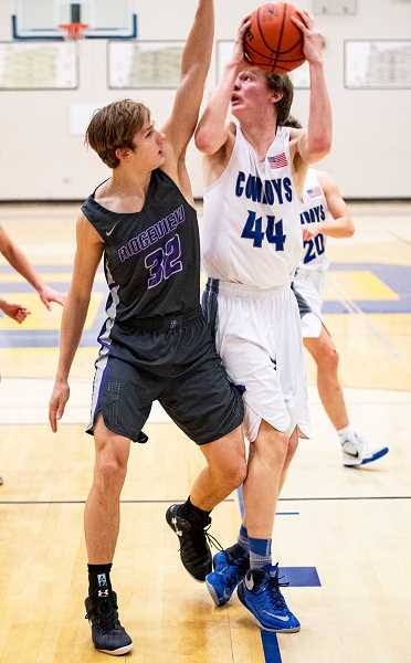 LON AUSTIN/CENTRAL OREGONIAN - Miles Chaney goes up for a shot against Ridgeview defender Taylor Moon. Chaney made the shot, and the Cowboys won the game 60-35 for their first Intermountain Conference win.