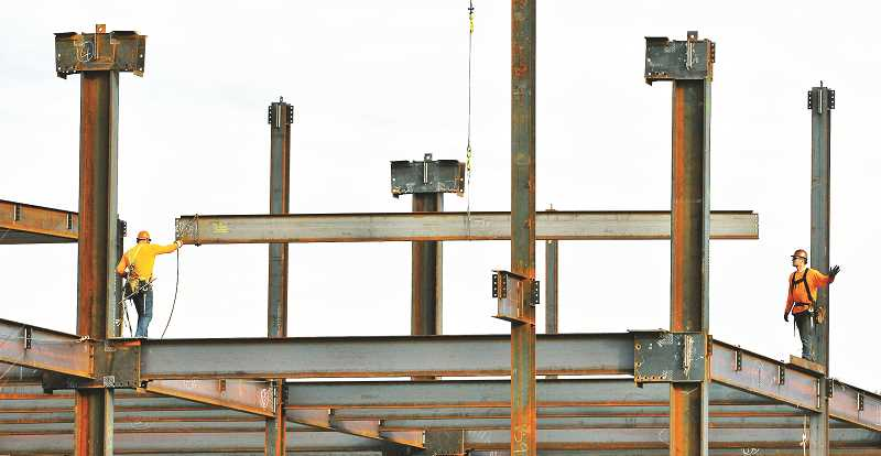 GARY ALLEN - Iron workers lower I-beams into position last week that will be the superstructure for the addition to Providence Newberg Medical Center.