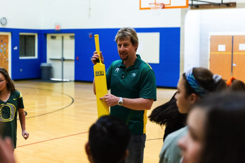 STAFF PHOTO: CHRISTOPHER OERTELL - Teacher Pete Hansen shows his sixth-grade students how to play cricket at Tom McCall Upper Elementary School in Forest Grove on Thursday, Jan. 24.