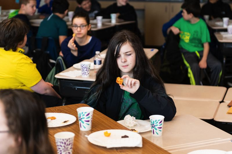 STAFF PHOTO: CHRISTOPHER OERTELL - Sophia O'Shea, 12, checks out a BBQ-flavored cracker during her sixth-grade class' celebration of Australia Day at Tom McCall Upper Elementary School.