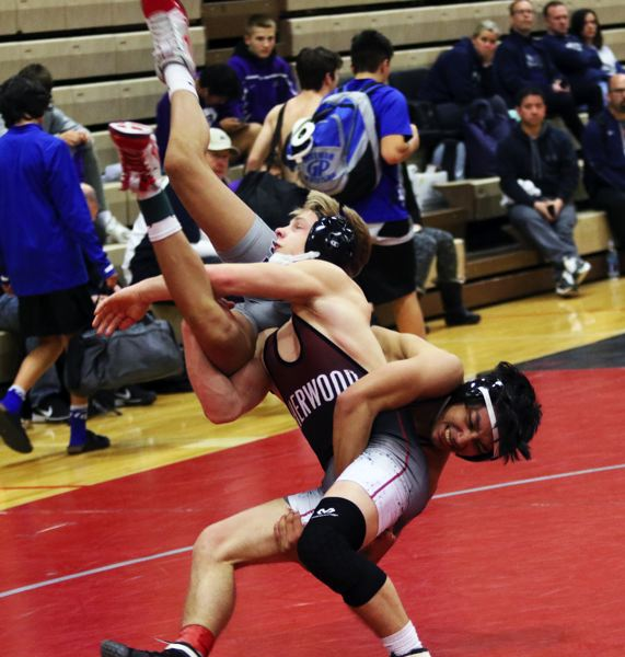 TIMES PHOTO: DAN BROOD - Sherwood High School senior Gaven Jolley throws Wilsonville's Isaac Quesada during their 126-pound championship match at the Winter Warriors Memorial Invitational.
