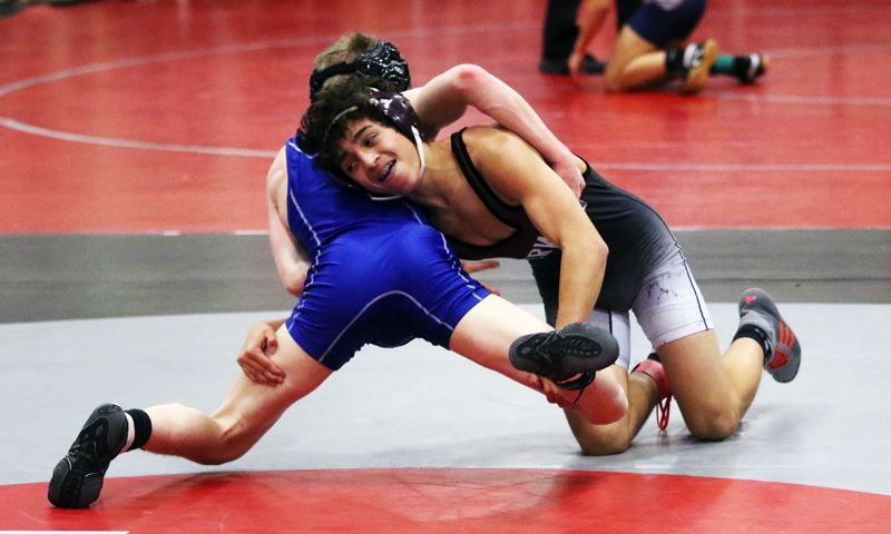 TIMES PHOTO: DAN BROOD - Sherwood freshman Ethan Ritchie (right) looks to get control against Houston Miner of Grants Pass during their 106-pound title match at Saturday's Winter Warriors Memorial Invitational.