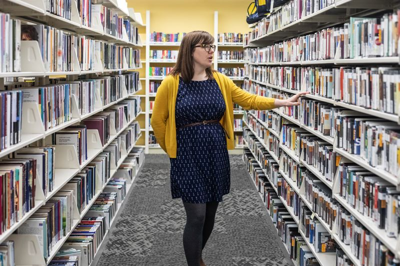 TRIBUNE PHOTO: JONATHAN HOUSE  - Electronic content librarian Kady Ferris browses the stacks of physical media that are being sorted for distribution at the Isom Operations Center, a closed-to-the-public facility next to the Wonder Ballroom in Portland.