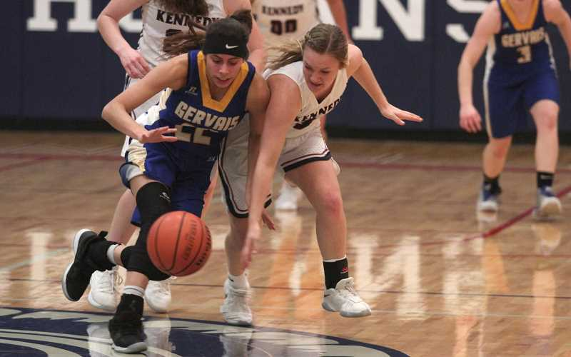 PAMPLIN MEDIA GROUP: PHIL HAWKINS - Gervais junior Isabel Vasquez fights with Kennedy sophomore Elise Suing for control of a loose ball in Friday nights 53-40 win for the No. 1 Trojans.