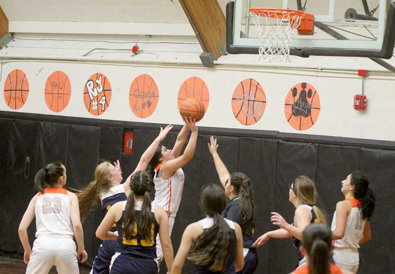 STEELE HAUGEN - Nena Mendoza finishes a drive to the hoop with Sheridan defenders all around her.