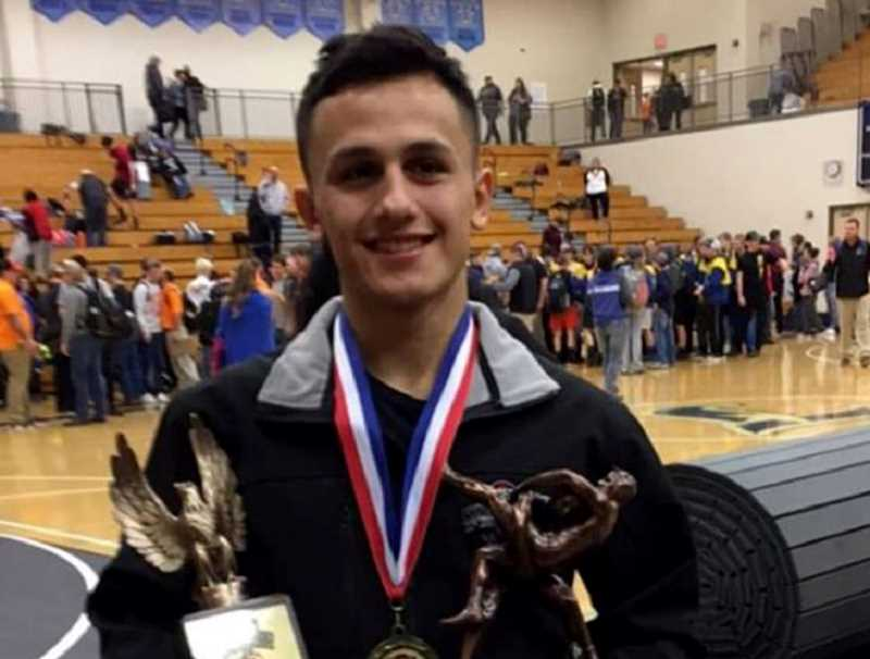 SUBMITTED PHOTO - Lorenzo Vasquez holds his 120-pound first-place and outstanding wrestler trophy after winning the Reser Tournament of Champions.