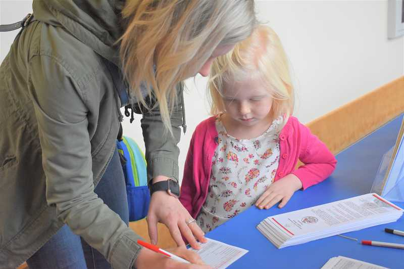 ESTACADA NEWS PHOTO: EMILY LINDSTRAND - A family signs up to participate in the Dolly Parton Imagination Library. The program connects children with books every month until their fifth birthday.