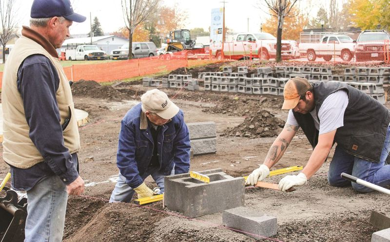 STAFF PHOTO: JASON CHANEY - Kiwanis club members Larry Penington, Gary Romine and Corey Lopez work on construction of a splash pad in Madras last fall. It's one of many charitable works led by service clubs throughout Oregon and the world.