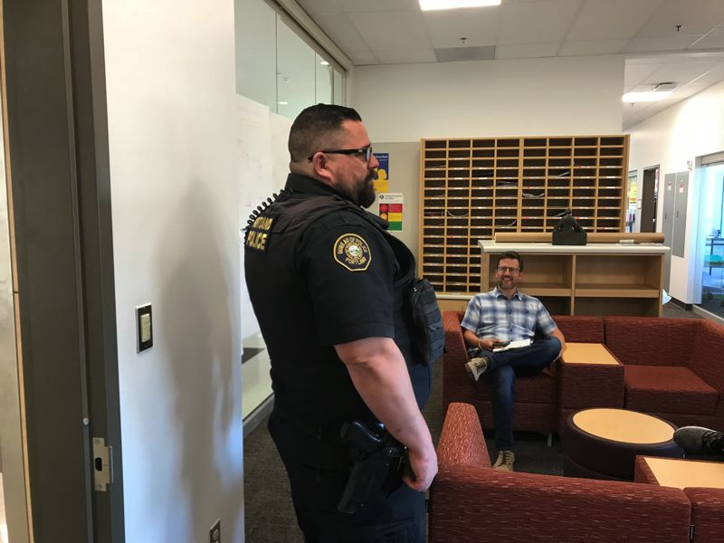 PAMPLIN MEDIA GROUP FILE PHOTO - A school resource officer at Franklin High School talks with a teacher late last year, as PPS board members discussed possible changes to the resource officer program.