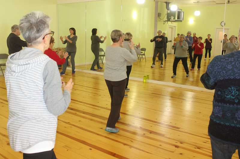 SUSAN MATHENY/MADRAS PIONEER - Carolyn Harvey, center in mirror, leads tai chi exercises at the Thursday class.