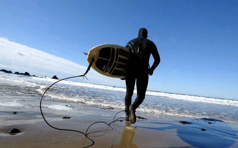 FILE PHOTO  - A surfer heads out to catch waves off the Oregon Coast.