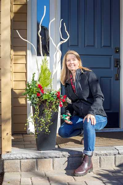 REVIEW PHOTO: JONATHON HOUSE - Janette Gallagher of Palisades Planters displays a recently finished seasonal winter planter at a client's house.