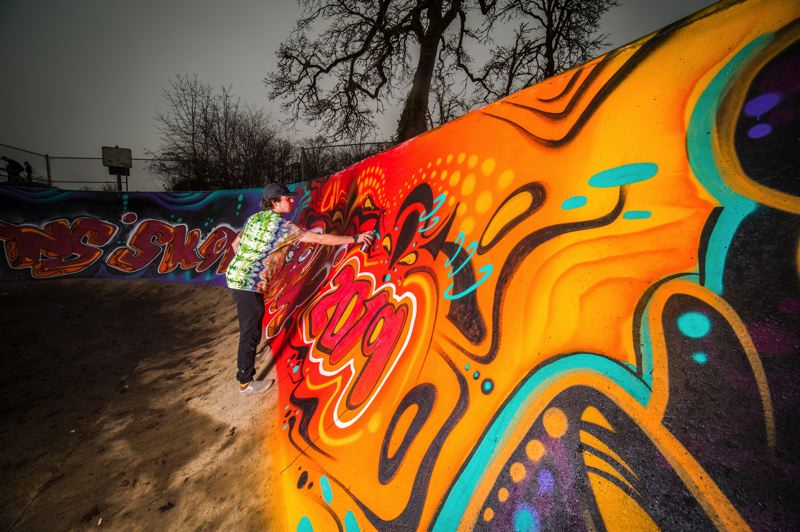 PHOTO COURTESY OF JACOB RASCON WITH KOALATY PHOTOS & FILM - Quinn Segal, 19, works on a mural in the St. Helens Skate Park at McCormick Park in January. The mural took four days to complete and the design was original.