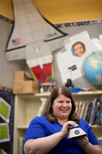 TIMES PHOTO: JAIME VALDEZ - ulie Wright holds up a NASA capsule shortly after teaching a group of fifth-graders about space and the astronauts who flew in those missions.