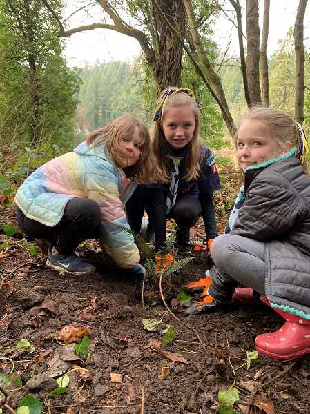 SUBMITTED PHOTO - Annie Weber, Emerson Lewis and Sarah Firmin plant a sword fern during a recent stewardship work party in the Lily Bay Natural Area.