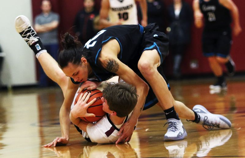 TIMES PHOTO: DAN BROOD - Sherwood High School sophomore Asher Krauel (bottom) and Century senior Daniel Berger battle over a loose ball during Wednesday's Pacific Conference contest.