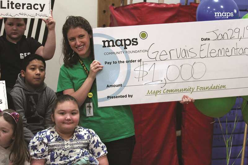 PHIL HAWKINS - Gervais Elementary School music teacher Courtney Karns displays her honorary $1,000 check from Maps Community Foundation after the Gervais community helped make her fundraising project the most voted for project in this year's Teacher Grant Program.