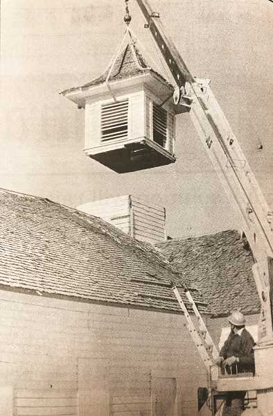 CENTRAL OREGONIAN - Feb: 3, 1994: Dave Franke, of Wrangler Construction, carefully lifts the cupola from the top of Cain Hall at the Crook County Fairgrounds Thursday morning. Cain Hall is condemned and scheduled for demolition. Although there are no immediate plans for the cupola, it may possibly be restored and mounted on another building.