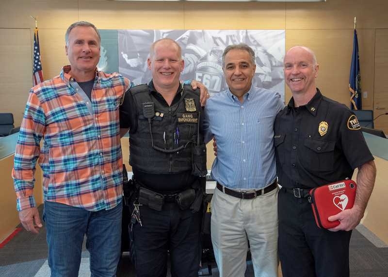 COURTESY OF TVF&R - Bystander Kevin Fabrycki, Portland Police Bureau Officer Jason Hubert, Ali Moghaddampour and TVF&R North Division Chief Allen Kennedy pose for a photo during a reunion on Jan. 28 at the main TVF&R headquarters in Tigard. Moghaddampour went into cardiac arrest and was saved by a combined effort of Fabrycki and the off-duty first-responders.