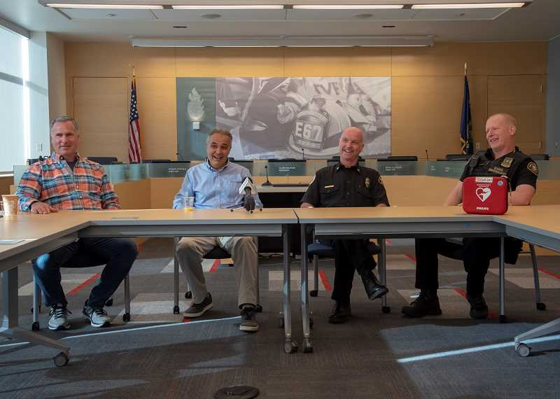 COURTESY OF TVF&R - Kevin Fabrycki, left, Ali Moghaddampour, TVF&R North Division Chief Allen Kennedy and Portland Police Bureau Officer Jason Hubert chat with the media on Jan. 28 during a reunion at the main TVF&R headquarters in Tigard. Moghaddampour went into cardiac arrest last August and was saved by the combined efforts of Fabrycki and the off-duty first-responders.