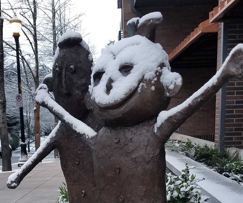 REVIEW PHOTO: GARY M. STEIN - Amyas and Soleil enjoy their snow day Tuesday. The Gallery Without Walls sculpture sits at the corner of First Street and Evergreen Road in downtown Lake Oswego.