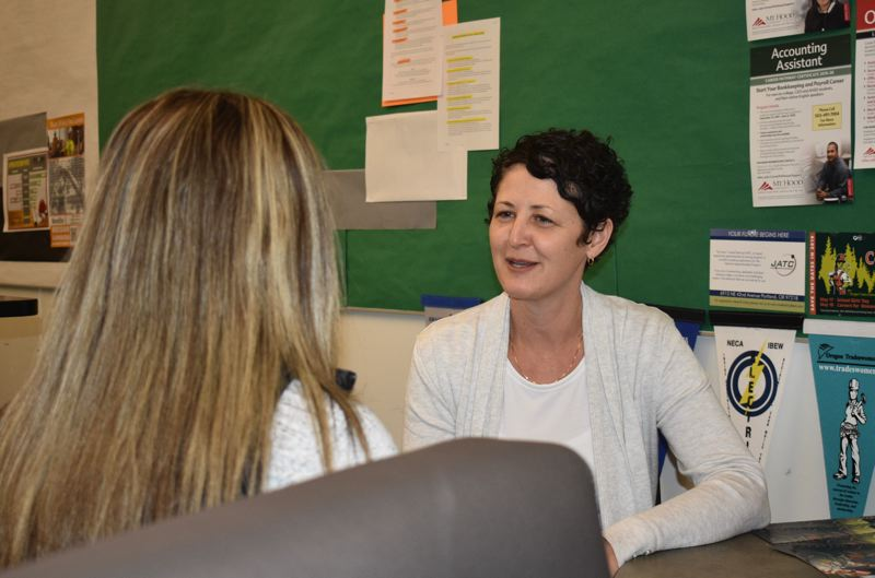 OUTLOOK PHOTO: TERESA CARSON - Ina Avendano Howe, the new career internship coordinator at Reynolds High School, talks to a student about her plans to become a firefighter.
