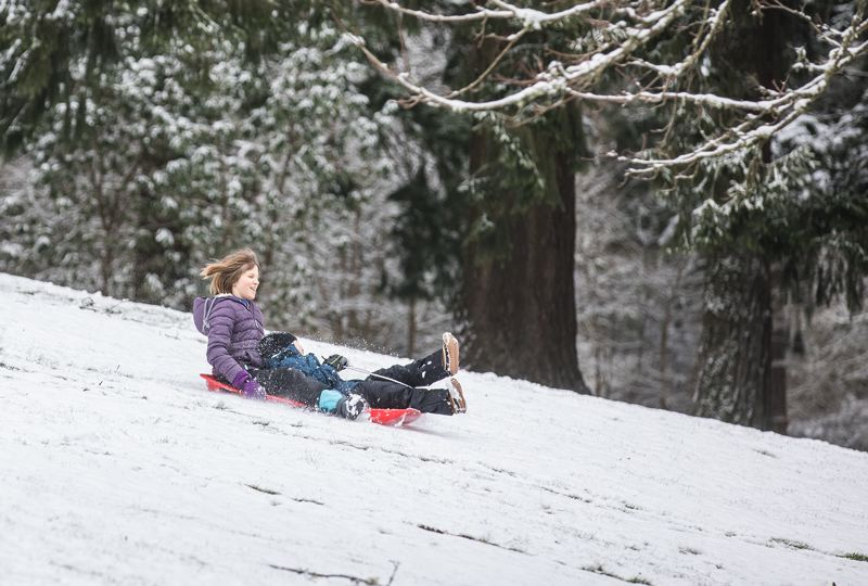 PAMPLIN MEDIA GROUP: JONATHAN HOUSE - Riley Richards and Will Johnson take advantage of snow at Washington Park for some sledding Tuesday, Feb. 5.